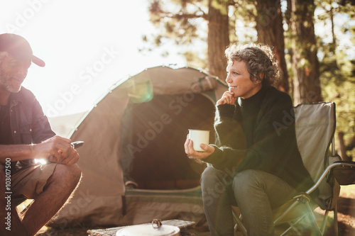 In de dag Kamperen Relaxed couple sitting outside tent while camping nearby lakesid
