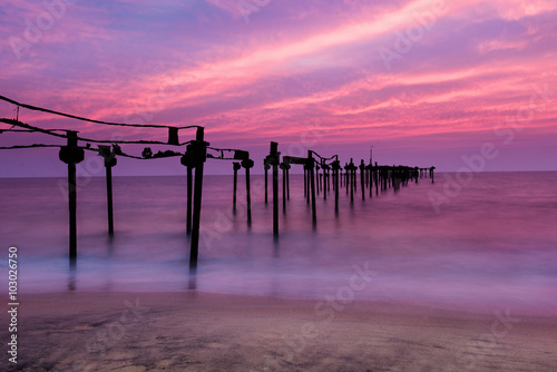 Fotobehang Candy roze Long exposure sea pier with beautiful sunset