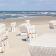 Ein leerer Sandstrand mit Strandkörben lädt zu einem Spaziergang entlang der Wellen ein.