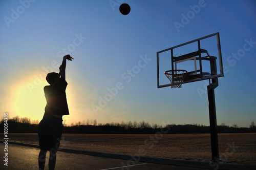 Silhouette of a Teen Boy shooting a Basketball Wallpaper Mural