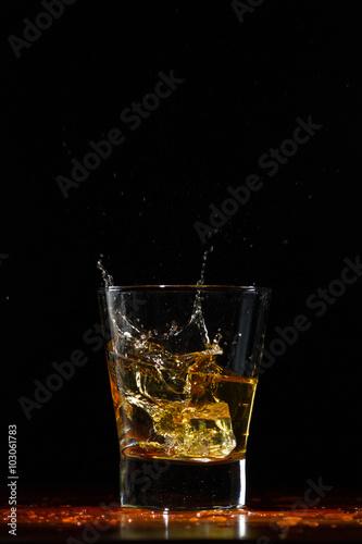 Whiskey splash in glass on black