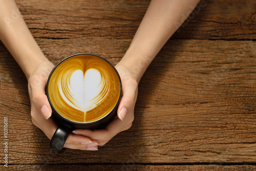 Wall Murals Cafe Woman holding cup of coffee latte, with heart shape