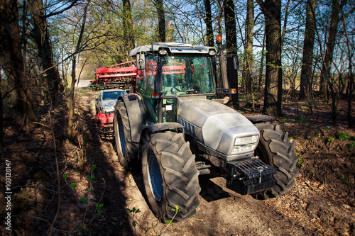 Fototapety, obrazy: side view of tractor on big wheels on soil road in forest