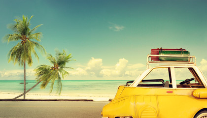 Fototapeta Travel destination: vintage classic car parked near the beach with bags on a roof - Honeymoon trip in summer