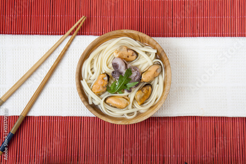 Noodles with mussels and octopus in wooden plate on a red makisu Wallpaper Mural