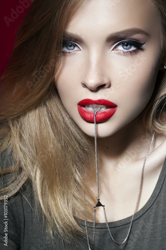 Valokuva  beautiful girl with red lips holding chain in the lips
