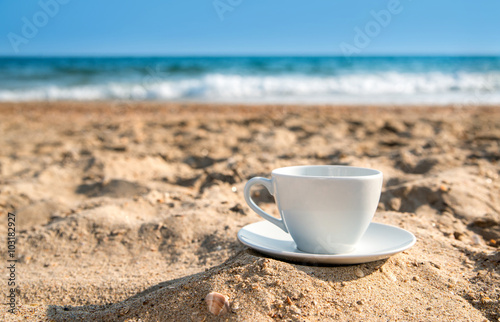 white cup with tea or coffee on sand beach front of sea
