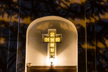 Christian Catholic Cross On The Facade Of The Church At Night. Lamp Above The Door