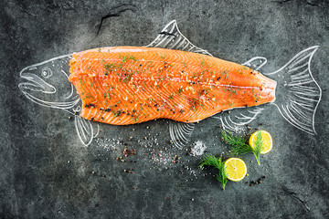 Naklejka raw salmon fish steak with ingredients like lemon, pepper, sea salt and dill on black board, sketched image with chalk of salmon fish with steak