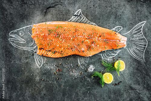 Photo sur Aluminium Poisson raw salmon fish steak with ingredients like lemon, pepper, sea salt and dill on black board, sketched image with chalk of salmon fish with steak