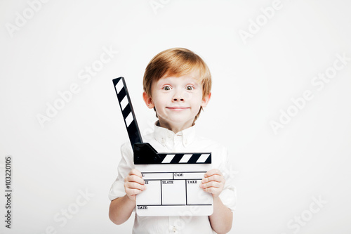 Little cute emotional boy with cinema clapper