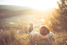Arefree Happy Woman Lying On Green Grass Meadow On Top Of Mountain Edge Cliff Enjoying Sun On Her Face.Enjoying Nature Sunset.Freedom.Enjoyment.Relaxing In Mountains At Sunrise.Sunshine.Daydreaming