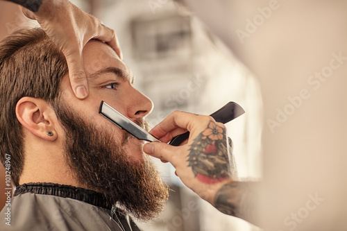 Платно Barber with old-fashioned black razor.