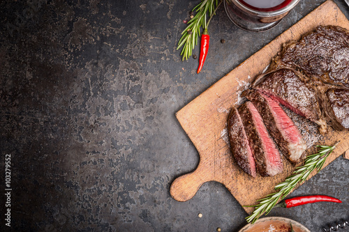 Spoed Foto op Canvas Steakhouse Sliced medium rare grilled steak on rustic cutting board with rosemary and spices , dark rustic metal background, top view, place for text