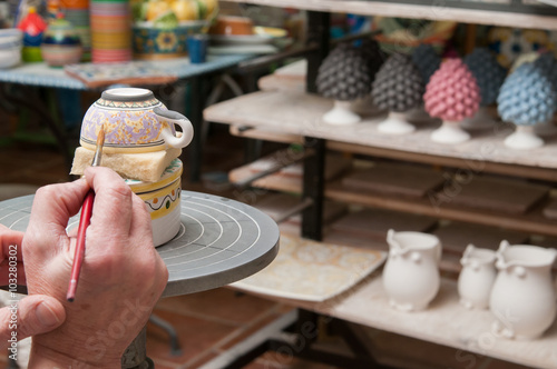 Fotografía  A pottery decorator finishing a ceramic small cup with floral motifs in his work
