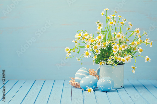 Photo  Easter holiday decoration with daisy flowers and painted eggs on wooden blue tab