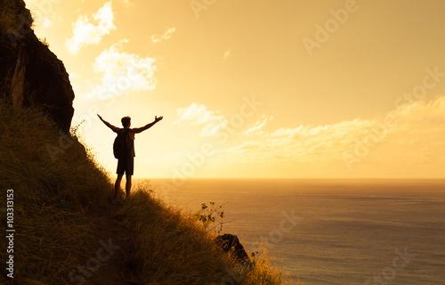 Fotografía  Happy man on top a mountain reaching his army out toward the horizon