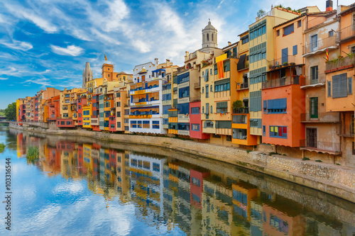 Colorful yellow and orange houses and famous house Casa Maso reflected in water river Onyar, in Girona, Catalonia, Spain. Church of Sant Feliu and Saint Mary Cathedral at background.