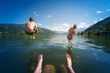 Girl And Boy Jumping In Lake W...
