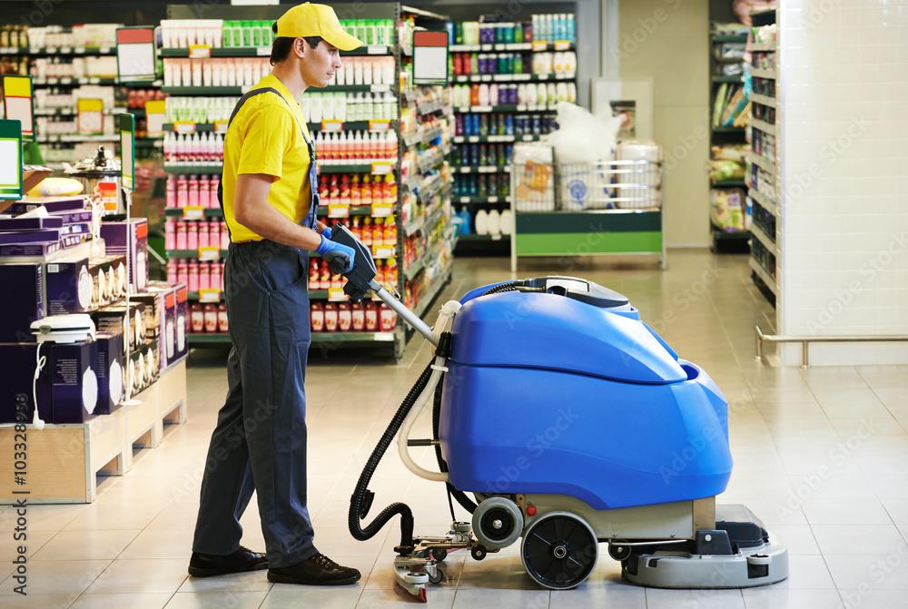 Fototapeta worker cleaning store floor with machine