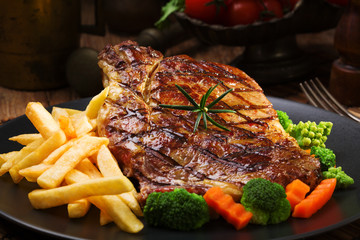 Panel Szklany Podświetlane Do steakhouse Grilled beef steak served with French fries and vegetables on a