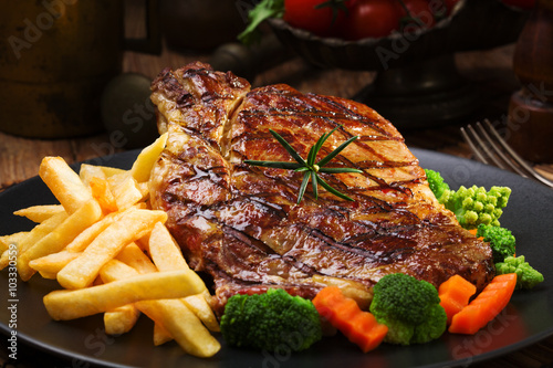 Grilled beef steak served with French fries and vegetables on a - 103330559