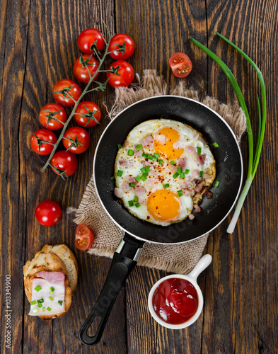 Fried eggs with ham and onion on wooden background.