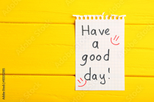 Photo  Piece of note paper on yellow wooden background