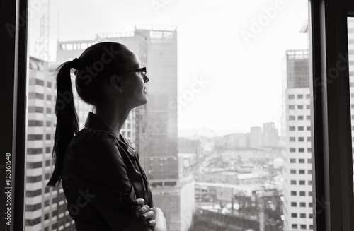 Fotografía  Thoughtful woman looking out her city window.