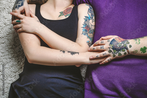 Mehndi Hands Couple : Young couple in love tattoos cuddling and holding hands on the