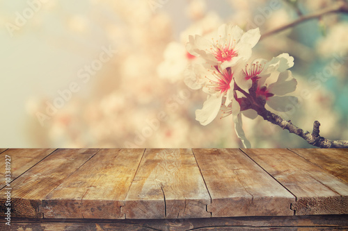 Foto op Plexiglas Retro wooden rustic table in front of spring white cherry blossoms tree. vintage filtered image. product display and picnic concept