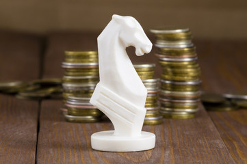 chess piece horse and coins on a wooden background