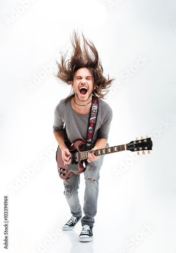 Photo  Crazy young man shaking head and playing electric guitar