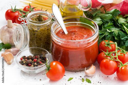 Fotografie, Obraz  tomato sauce, pesto and ingredients for pasta on a white table
