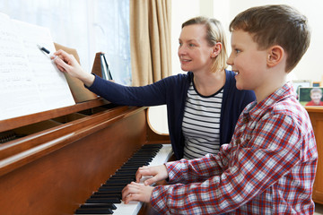 FototapetaBoy With Music Teacher Having Lesson At Piano