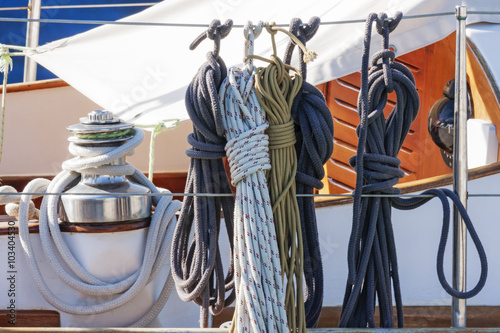 Spoed Foto op Canvas Zeilen Colorful nautical accessories with ropes, pulley and chromed winch on a well equipment wooden sailboat