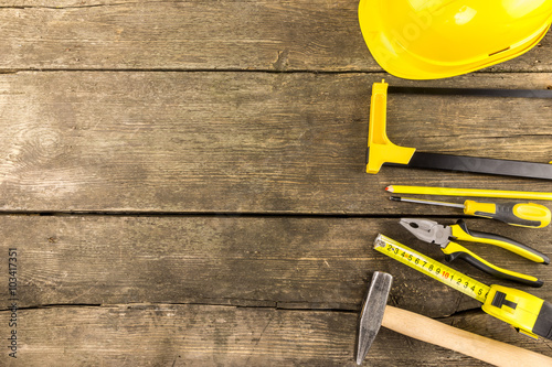 Fototapeta Set of industrial work  tools laid out on a rustic wooden table with copy space  including measuring tape, screwdriver, pliers protective helmet, carpenter pencil, hammer and a hacksaw. obraz na płótnie