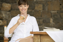 A Woman Drinking A Glass Of Wi...