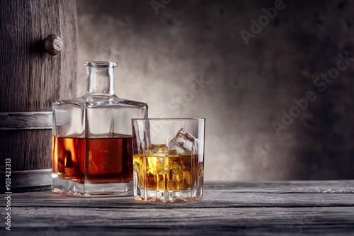 Photo  Square decanter and a glass of whiskey with ice