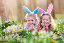 Kids On Easter Egg Hunt In Blooming Spring Garden