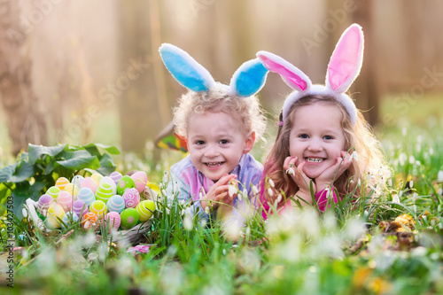 Photo  Kids on Easter egg hunt in blooming spring garden