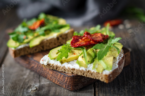 Fototapeta Healthy toast with goats cheese, avocado, arugula and sun dried tomatoes on rustic wooden table. Selective focus obraz