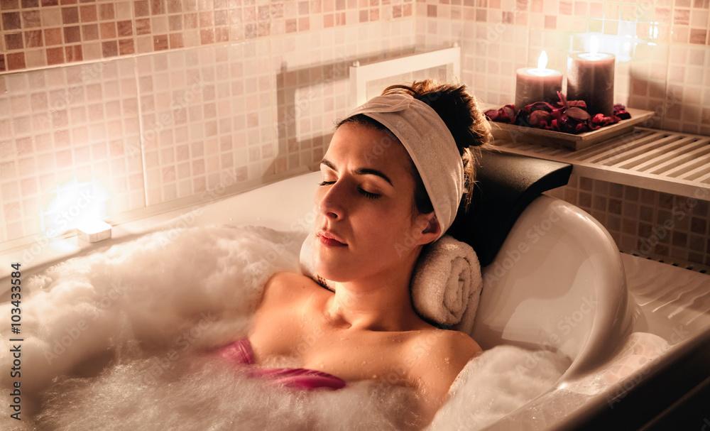 Fototapeta Woman lying in tub doing hydrotherapy treatment