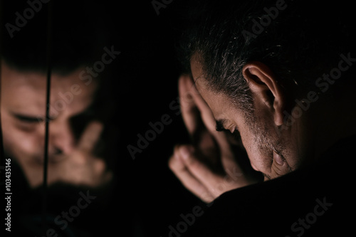 Photo  Man in despair, sad and lonely resting his head on a hand, in front of mirror