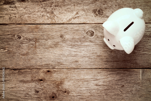 Photo  Piggy bank on the old wooden background.