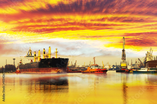 Garden Poster Coral Big ship with escorting tugs leaving port at sunset.