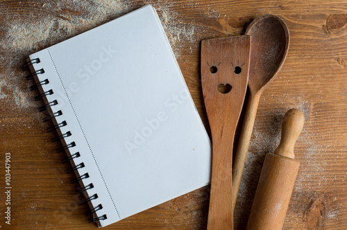 Fotografía  Open recipe book with wooden spoon, rolling pan and spatula