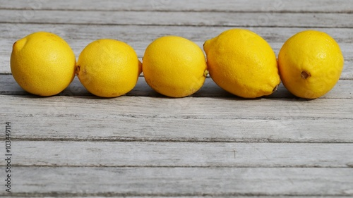 Five yellow lemons lined up on a wooden table