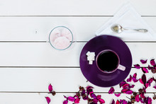 Cup Of Tea Or Coffee On Violet Plate, Silver Spoon, Marshmallow In Glass Vase, Lump Sugar, Violet Purple Dry Decor Scattered On White Colored Wooden Table,  Top View