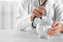 Doctor Hands With Piggy Bank Closeup